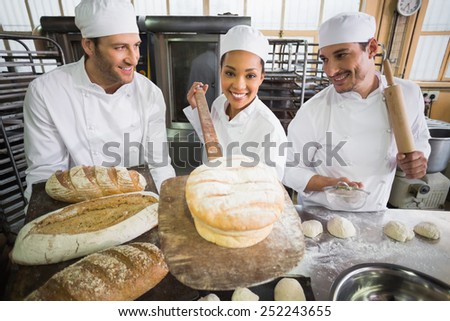Team of bakers working together in the kitchen of the bakery - stock photo