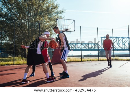 Team of basketball players making an action together. - stock photo