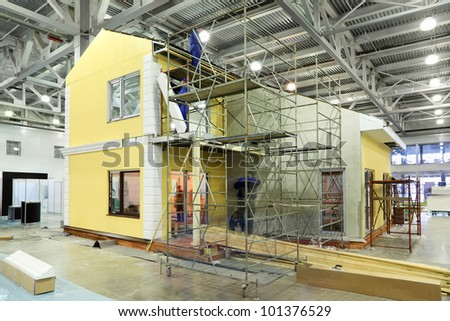 Team of builders build two-storey yellow cottage in large hall