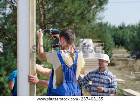 Team of builders installing insulated wall panels on a residential building site watched by the architect, engineer, or foreman - stock photo