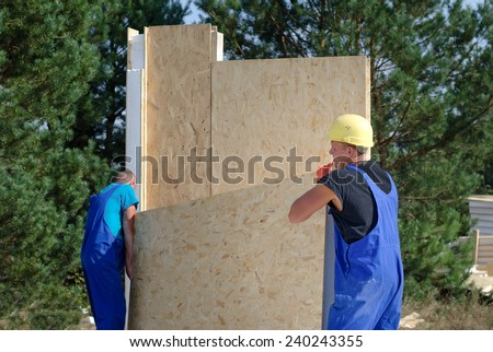 Team of builders on site carrying an insulated wooden wall panel ready for installation, new build residential house - stock photo