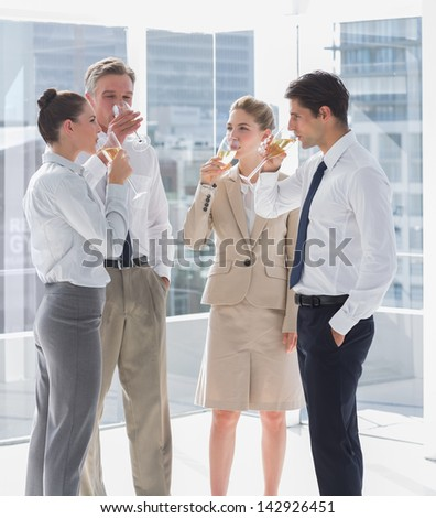 Team of business people drinking champagne in the workplace - stock photo