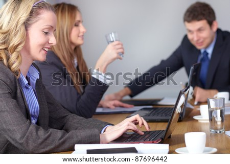 Team of 3 business people during meeting, sitting at big conference table. One female works on her laptop. - stock photo