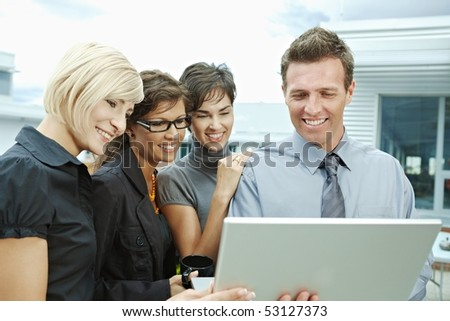 Team of business people looking at laptop computer outdoor in front of office building. - stock photo