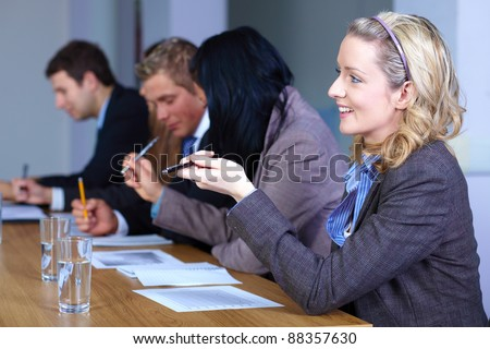 Team of 5 business people sitting at conference table and working on some calculations, blonde businesswoman on foreground point to someone on the opposite site of table - stock photo
