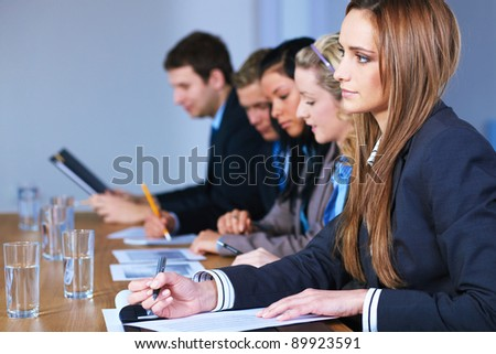 Team of 5 business people sitting at conference table during meeting - stock photo