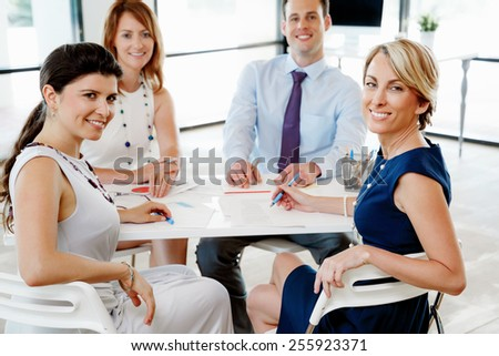 Team of business people sitting in office - stock photo