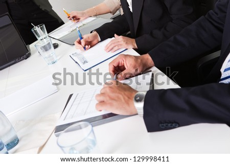 Team of business people taking notes at the meeting