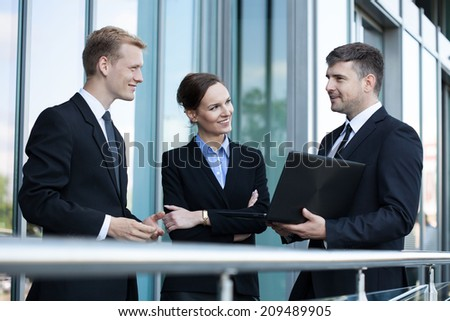 Team of business people talking in front of office building - stock photo