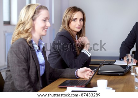 Team of 2 business people working on their laptops, sitting at conference table - stock photo
