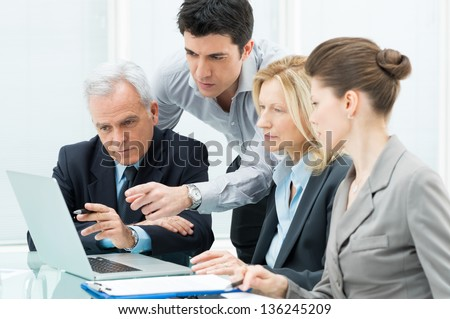 Team Of Business People Working Together On A Laptop - stock photo