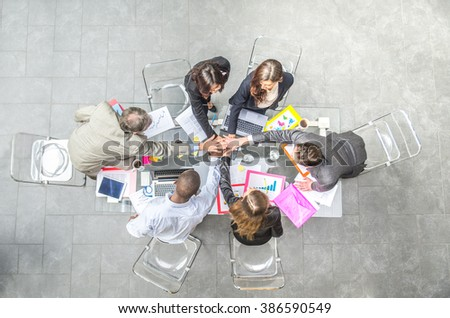 Team of businessmen joining hands during a successful meeting - CEO and managers in a company office, concepts about team work and unity, view from above - stock photo
