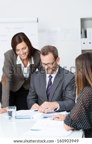Team of businesspeople in a meeting with focus to a smiling woman standing over the shoulder of a man in glasses as they discuss paperwork spread out on the desk - stock photo