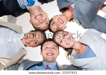 Team of businesspeople joining heads together in the office - stock photo