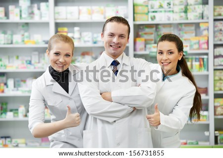 Team of cheerful pharmacist chemist standing in pharmacy drugstore - stock photo