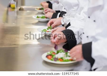 Team of Chef's preparing salads in kitchen - stock photo