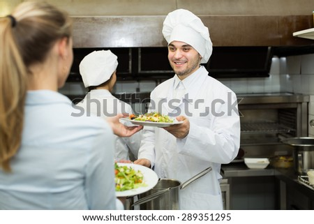 Team of chefs and waitress at the work at restaurant kitchen - stock photo