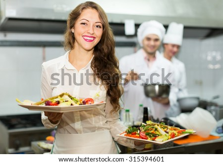 Team of chefs and young beautiful waiter at restaurant kitchen - stock photo