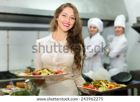 Team of chefs and young beautiful waiter at the restaurant kitchen - stock photo