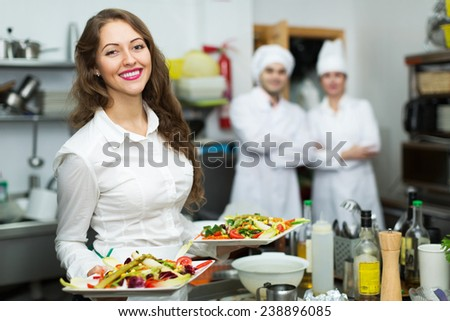 Team of chefs and young beautiful waiter in restaurant kitchen - stock photo