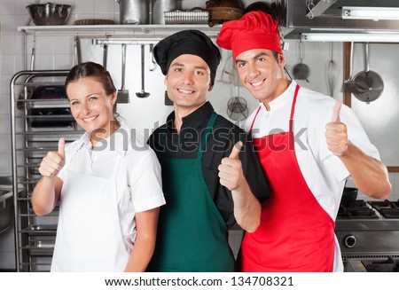 Team of chefs giving thumbs up in restaurant kitchen - stock photo