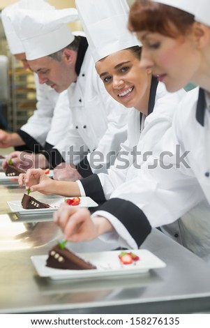 Team of chefs in a row garnishing dessert plates one girl smiling at camera in busy kitchen