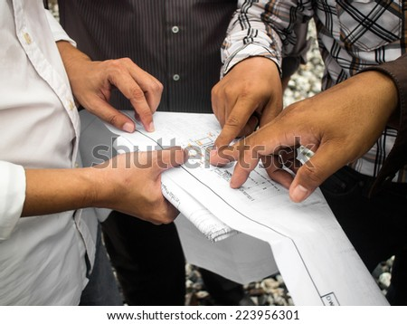 Team of civil people in group on construciton site check documents and business workflow - stock photo