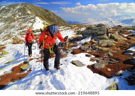 Team of climbers ascend a snow covered trail on the mountain - stock photo