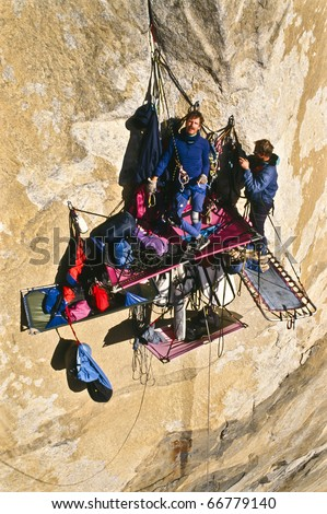 Team of climbers bivouacked in their portaledges on the side of a bigwall. - stock photo
