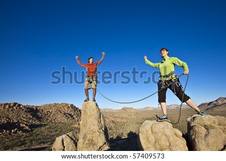 Team of climbers celebrate on the summit of a rock spire. - stock photo