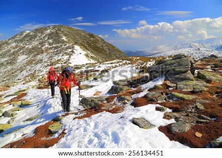 Team of climbers follow a trail on mixed terrain in sunny winter day - stock photo