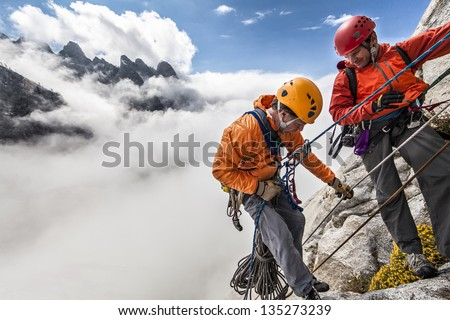 Team of climbers rappelling the cliff during a storm. - stock photo