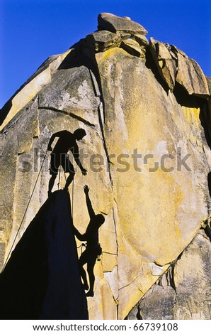 Team of climbers reaching the summit of a rock pinnacle. - stock photo
