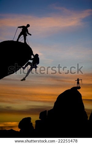 Team of climbers reaching the summit of a rock pinnacle in The Sierra Nevada Mountains, California. - stock photo