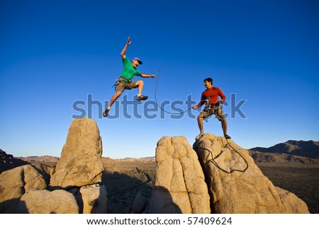 Team of climbers reaching  the summit of a rock spire. - stock photo