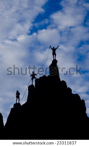 Team of climbers reaching the summit of a rock spire in The Sierra Nevada Mountains. - stock photo
