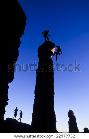 Team of climbers reaching the summit of a sandstone pinnacle in Canyonlands National Park, Utah. - stock photo