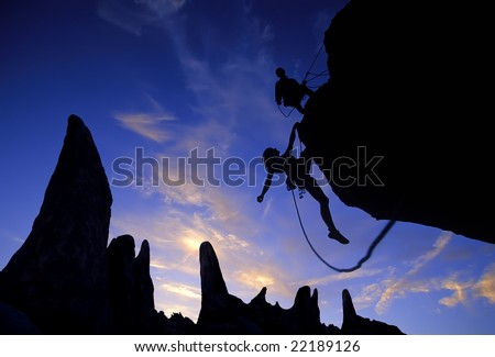 Team of climbers reaching the summit of an overhanging rock pinnacle in The Sierra Nevada Mountains, California. - stock photo