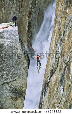 Team of climbers reaching the summit of The Lost Arrow Spire, in Yosemite National Park, by tyrolean traverse as Yosemite Falls roars behind them. - stock photo