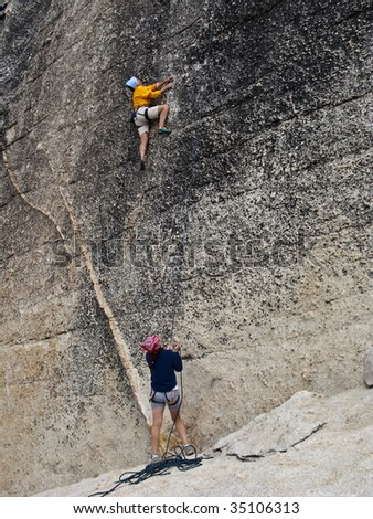 Team of climbers scale a steep rock face in The Sierra Nevada Mountains, California. - stock photo
