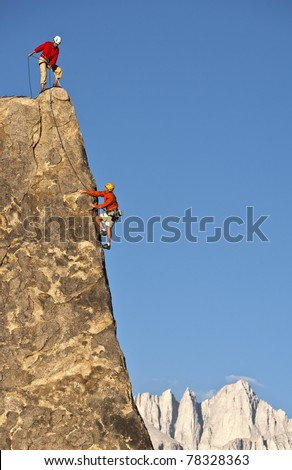 Team of climbers struggle to reach the summit of an challenging rock pinnacle. - stock photo