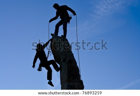 Team of climbers struggle to reach the summit of an overhanging rock pinnacle. - stock photo