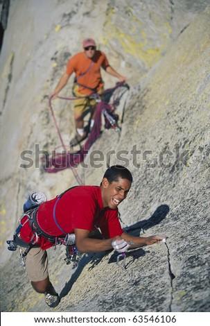 Team of climbers struggle up a steep crack. - stock photo