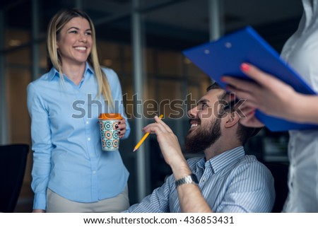 Team of colleagues enjoying coffee break in an office. - stock photo