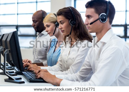 Team of colleagues working on computer with headset in the office