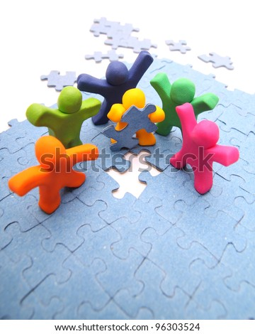 team of colorful plasticine people solving the puzzle together - teamwork concept - isolated on white - stock photo