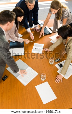 Team of confident people pointing to a business project at seminar - stock photo