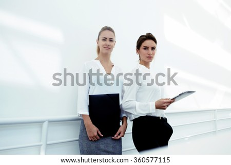 Team of confident women with portable touch pad and documents in hands posing in modern office interior,professional female employer with digital tablet standing with secretary while preparing meeting - stock photo