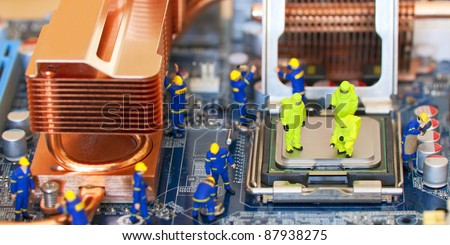Team of construction workers repairing computer - stock photo