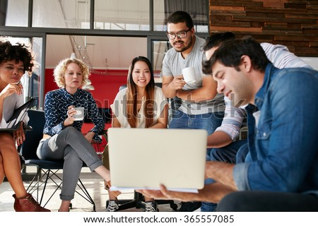 Team of creative people looking at colleague showing project plan on his laptop. Diverse group of young people having a meeting at the office. They are discussing about new project. - stock photo